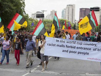 """Manifestantes com bandeiras e um cartaz que diz """"No país da Copa do Mundo, shoppings racistas proíbem a entrada de pessoas negras e pobres""""."""