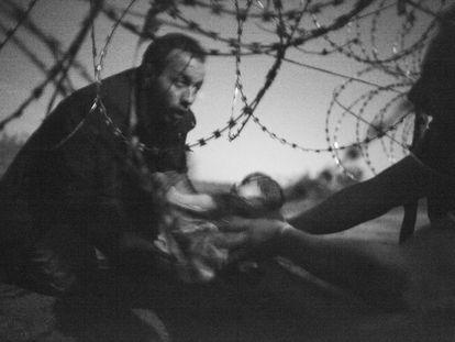Esta imagem do fotógrafo australiano Warren Richardson foi considerada a melhor foto do ano na 59a edição do World Press Photo, a maior premiação do fotojornalismo mundial. A fotografia, em preto e branco, mostra um homem passando um bebê pela cerca de arame farpado em Roeszke, na fronteira entre a Sérvia e a Hungria, em 28 de agosto de 2015.