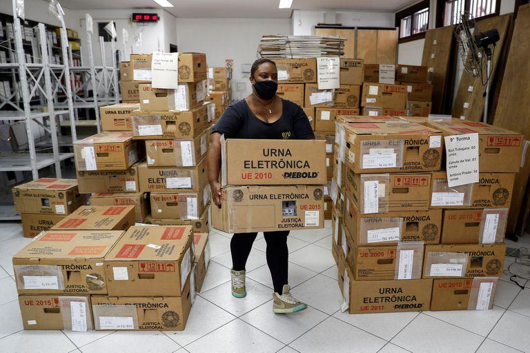 Funcionária do Tribunal Regional Eleitoral de São Paulo transporta urnas eletrônicas a um lugar de votação na capital paulista, no sábado, véspera do primeiro turno das eleições municipais 2020.