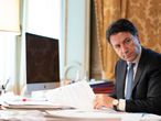 """This photo taken and handout by the press office of Palazzo Chigi on March 26, 2020 shows Italian Prime Minister, Giuseppe Conte taking part from his office in Rome in a video conference as part of an extraordinary meeting of G20 leaders, during the country's lockdown following the COVID-19 new coronavirus pandemic. - Italian Prime Minister Giuseppe Conte is blocking a joint response that EU leaders are trying to put together to the coronavirus crisis, an Italian government source said on March 26. (Photo by Handout / Palazzo Chigi press office / AFP) / RESTRICTED TO EDITORIAL USE - MANDATORY CREDIT """"AFP PHOTO / PALAZZO CHIGI PRESS OFFICE"""" - NO MARKETING - NO ADVERTISING CAMPAIGNS - DISTRIBUTED AS A SERVICE TO CLIENTS"""