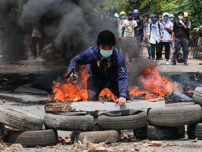 Ativista em uma barricada improvisada pelos manifestantes neste sábado em Rangum.