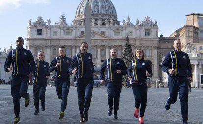 Integrantes da equipe de atletismo do Vaticano correm para a imprensa em frente à basílica de São Pedro.