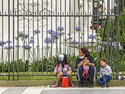 Mulher com seus dois filhos pede ajuda em uma rua de Buenos Aires, no dia 4 de dezembro.