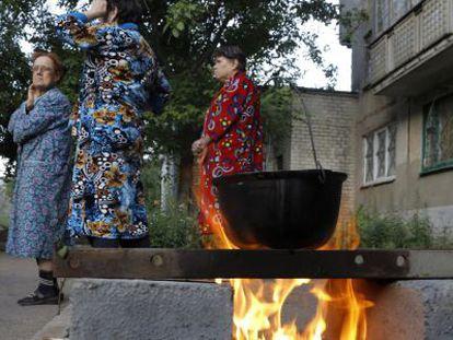 Um grupo de mulheres ferve água em uma rua de Slaviansk.