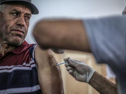 Palestino recebe a vacina Sputnik contra o coronavírus no campo de refugiados de Khan Younis, no sul da Faixa de Gaza.