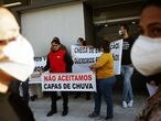"""Health workers wearing protective face masks hold a banner reading """"We do not accept rain covers"""" as they take part in a protest against the lack of personal protective equipment (PPE) during the coronavirus disease (COVID-19) outbreak, at the Tide Setubal public hospital in Sao Paulo, Brazil, April 17, 2020. REUTERS/Rahel Patrasso"""