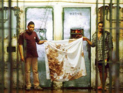 Detentos mostram panos sujos de sangue após o massacre, em outubro de 1992.