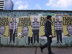 """A man walks past posters depicting Brazil's Economy Minister Paulo Guedes with the phrases """"Faria Loser"""", """"I hate poor people"""", """"It is a hell of a party"""" and """"Everybody wants to live, this way it doesn't work"""" at Faria Lima Avenue in Sao Paulo, Brazil August 30, 2021. REUTERS/Amanda Perobelli"""