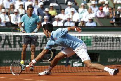 Djokovic estica-se para devolver uma bola a Nadal.