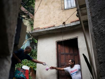 Voluntário entrega sabonete para um morador da favela da Rocinha, Rio de Janeiro, no dia 24 de março.