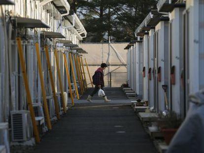 Mulher caminha pelas casas temporárias em Tamura, Fukushima.