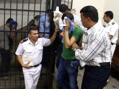 Os acusados escondem o rosto após a condenação no Cairo.