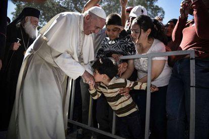 Uma criança beija ao Papa durante sua visita ao centro de emigrantes de Moria na ilha de Lesbos (Grécia), o 16 de abril de 2016.