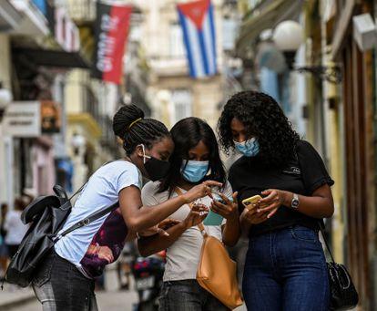 Três mulheres usam seus telefones celulares em Havana, em 14 de julho.