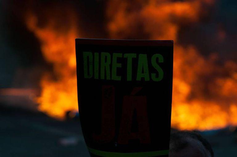 Manifestante com um cartaz em defesa de eleições antecipadas diretas, em Brasília. Ao fundo, barricada com fogo na Esplanada dos Ministérios.