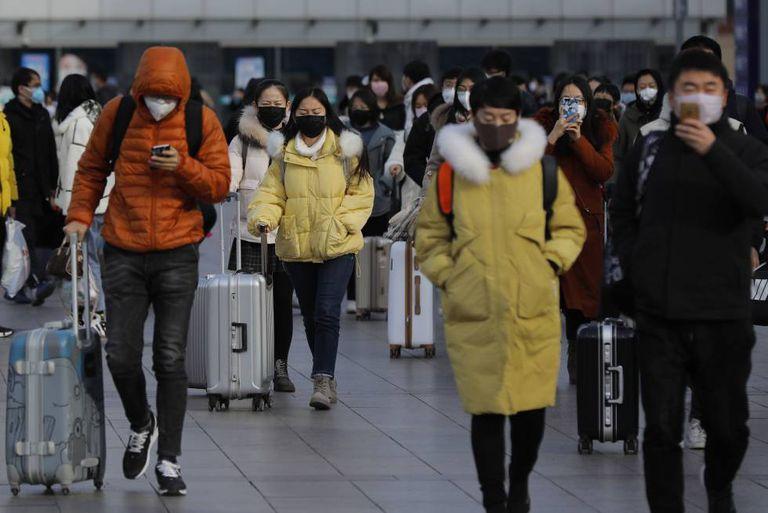 Um grupo de pessoas com máscara deixa uma estação ferroviária de Pequim, neste sábado.