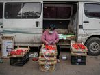 A vendor wearing a face mask as a preventive measure against the COVID-19 coronavirus sells strawberries on a street in Beijing on May 5, 2020, on the last day of a five-day national holiday. (Photo by NICOLAS ASFOURI / AFP)