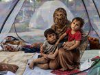 KABUL, AFGHANISTAN - AUGUST 12: Farzia, 28, who lost her husband in Baghlan one week ago to fighting by the Taliban sits with her children, Subhan, 5, and Ismael ,2,  in a tent at a makeshift IDP camp in Share-e-Naw park to various mosques and schools on August 12, 2021 in Kabul, Afghanistan. People displaced by the Taliban advancing are flooding into the Kabul capital to escape the Taliban takeover of their provinces. (Photo by Paula Bronstein/Getty Images)