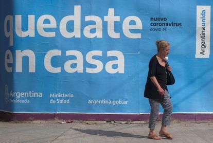 Uma mulher passa em frente a um cartaz governamental que pede à população que fique em casa.