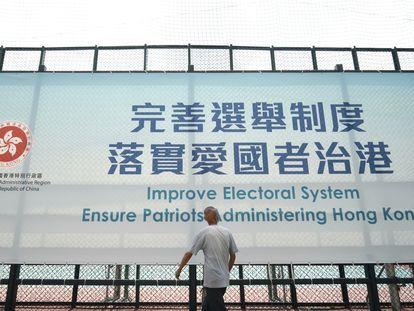 Um homem passa diante de um cartaz que promove a reforma eleitoral, nesta terça-feira, em Hong Kong.