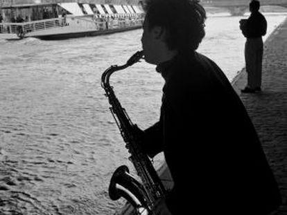 Um músico às margens do rio Sena, em Paris.