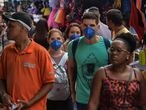 People wearing face masks as a preventive measure against the spread of the new coronavirus, COVID-19, are seen in downtown Sao Paulo, Brazil on March 16, 2020. - The Sao Paulo stock exchange closed down 13.9 percent Monday and the Brazilian real closed below five to the dollar for the first time ever in further fallout from the coronavirus pandemic. (Photo by NELSON ALMEIDA / AFP)