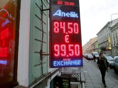 Um homem passa diante de uma casa de câmbio em Moscou, na Rússia, na qual se vê a queda abrupta do rublo.