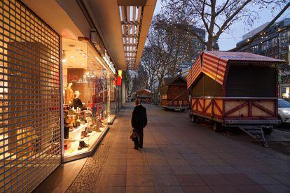 Mulher passa por vitrine de loja fechada em Berlim, nesta quarta.