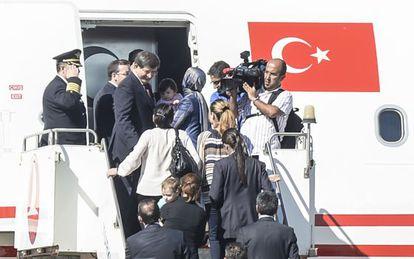 O primeiro-ministro turco, Ahmed Davutoglu (acima à esquerda), recebe os reféns libertados, em um avião em Sanliurfa.