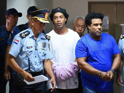 Ronaldinho aparece algemado ao lado do irmão ao chegar no Palácio da Justiça de Assunção, neste sábado.