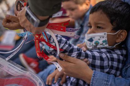 Um agente fronteiriço do Texas corta um bracelete que indica o status migratório do menino Santiago, que viajou com sua mãe de Honduras para solicitar asilo nos EUA.