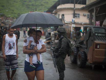 Moradores caminham pela Vila Kennedy durante operação do exército, nesta sexta.