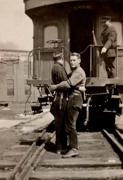Um casal se abraça, ao fundo há um trem com um maquinista que os observa. A data da foto é desconhecida, mas se sabe que é uma imagem estadounidense.