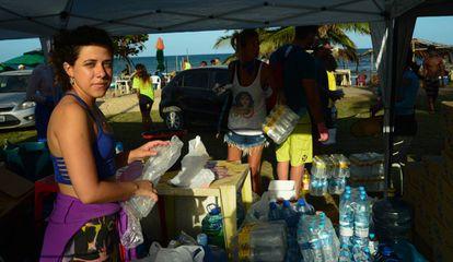 A estudante Camille Azevedo, 24 anos, ajuda na distribuição de equipamentos e alimentos para voluntários.