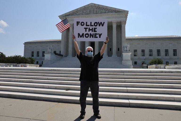 Manifestante diante da Suprema Corte com um cartaz em referência ao caso das finanças de Donald Trump,  na quarta-feira.