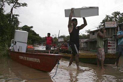 Moradores e a Defesa Civil do Acre tentar salvar seus pertences.