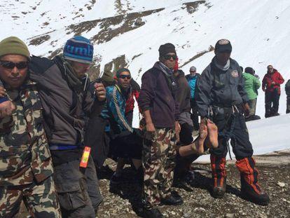 Membros das equipes de resgate transportam sobreviventes.