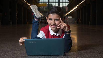 Antonio García Vicente, de 11 anos, posa com o computador no qual programa.