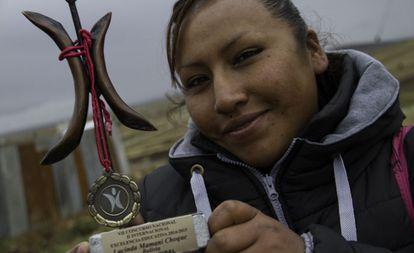 Lucinda exibe prêmio de excelência educativa que ganhou em 2014 da Fundação para a Integração e Desenvolvimento da América Latina.