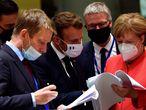El presidente Pedro Sánchez (izq.), el presidente francés, Emmanuel Macron, y la canciller alemana, Angela Merkel, examinan documentos durante la cumbre de la UE en Bruselas este lunes.