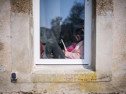 Menina lê dentro de casa em Lavau-sur-Loire, na França, durante quarentena.