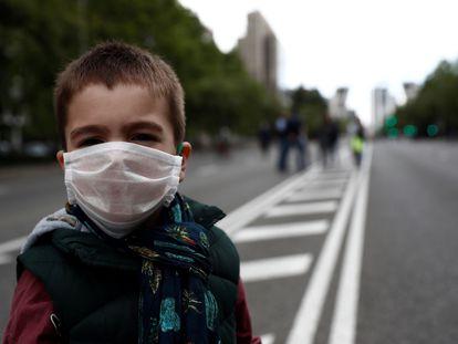 Um garoto com máscara, no sábado no Paseo de la Castellana, em Madri.