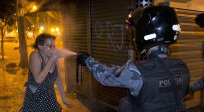 Policial Militar espirra spray de pimenta em mulher durante protesto no Rio de Janeiro, em junho de 2013.