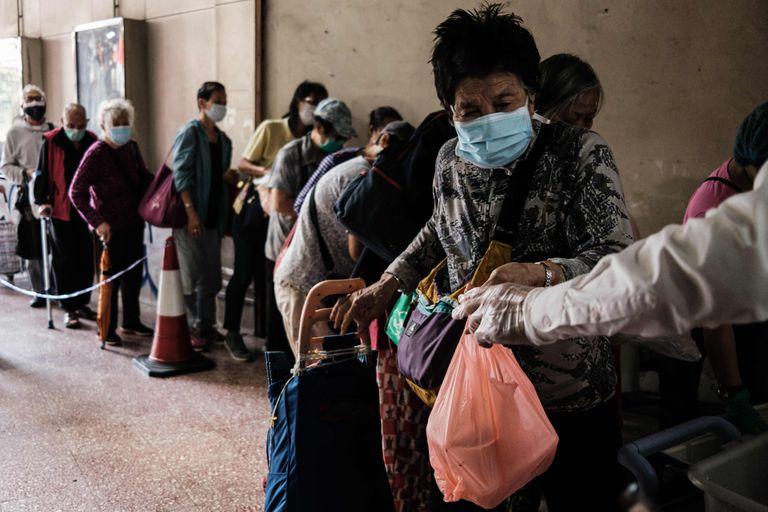 Pessoas fazem fila para pegar refeição doada em Hong Kong.