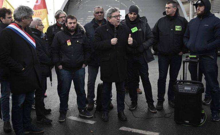 O líder esquerdista Jean-Luc Mélenchon fala com um grupo de ferroviários em Paris.