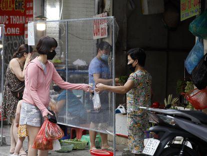 Mulher compra vegetais no mercado de Hanói, no Vietnã, nesta quinta-feira. Hanói acaba de relaxar das medidas de distanciamento social depois de dois novos meses de lockdown.
