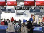 Pasajeros con máscaras en el aeropuerto de Praga, que ha comenzado una campaña de información para viajeros con posibles síntomas de coronavirus, este lunes.