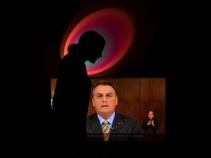 """Mulher grita """"Fora, Bolsonaro"""" enquanto presidente brasileiro discursa na TV."""