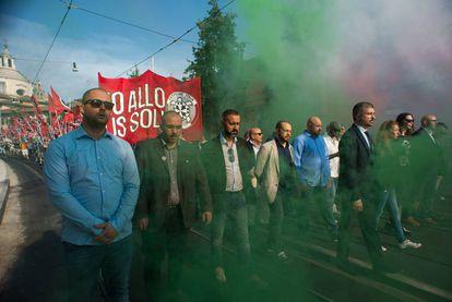 Simone Dei Stefano, com terno e gravata, encabeça uma manifestação anti-imigração.
