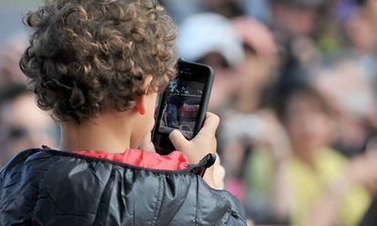 Uma criança usa um smartphone.